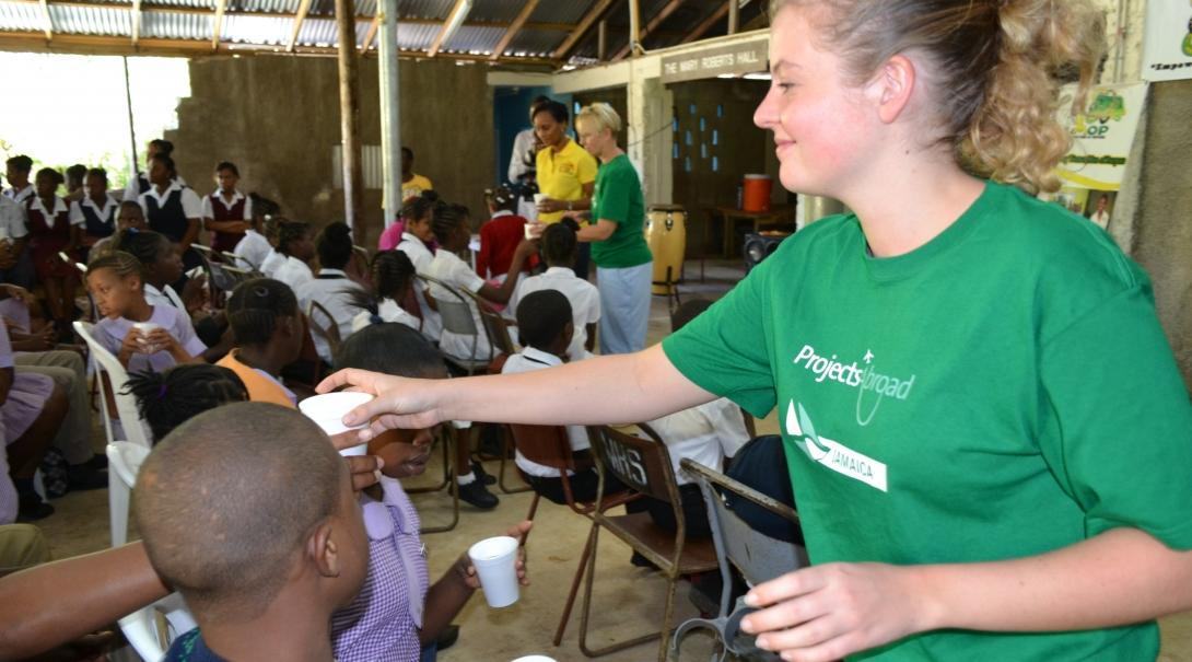 Psychology work experience in Jamaica shows Projects Abroad Childcare volunteer handing out hot drinks to school children during a HIV/Aids awareness presentation.
